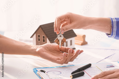 Fototapeta Real estate agent giving a key from new house to client in office obraz