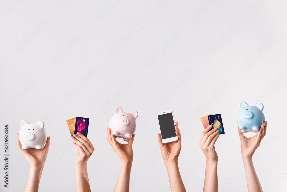Fototapeta Female hands with credit cards, piggy banks and mobile phone on light background. Concept of online banking