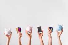 Female Hands With Credit Cards, Piggy Banks And Mobile Phone On Light Background. Concept Of Online Banking