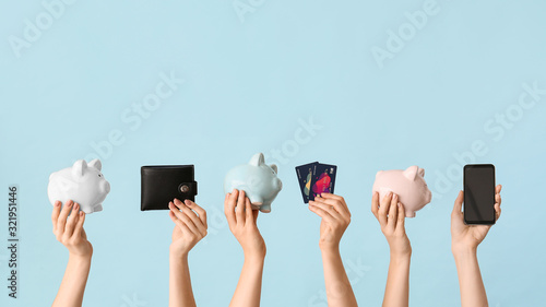 Stampa su Tela Female hands with piggy banks, credit cards, wallet and mobile phone on color background