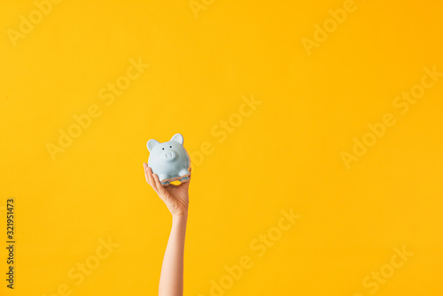 Fototapeta Female hand with piggy bank on color background obraz