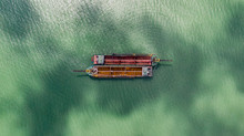 Old Fishing Boats On The Sea Off The Coast Of Malaysia From The Sky. Aerial View To Two Old Wooden Malaysian Fisher Boats On The Lebam River Near The City Of Singapore. Drone Capture At Johor Bahru