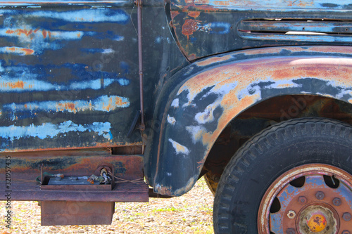 a rusted blue truck door panel and wheel