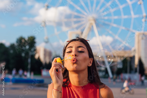 Obraz Beautiful young woman blowing soap bubbles outdoors - fototapety do salonu