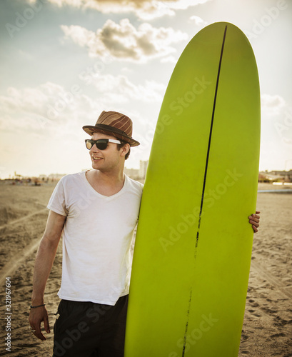young man on the beach with surf board - 321967604