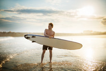 Young Man Walking On The Beach With A Surf Board