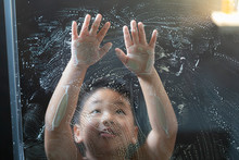 A Boy Plays With Soap Bubbles ...