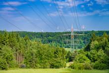 Stromleitungen Vor Blauem Himmel Die über Wald Mit Wiesengrund Führen.