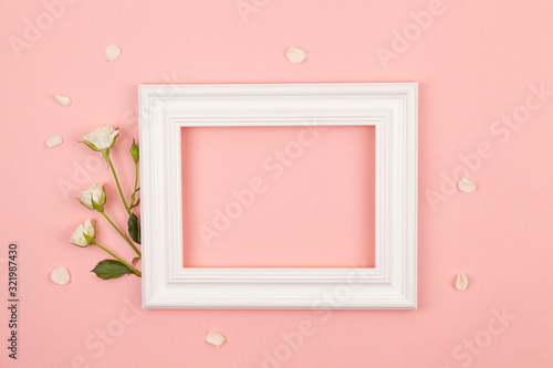 Fotografía White photo frame and rose flowers on a pink background