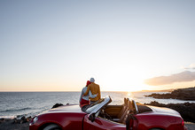 Couple Enjoying Beautiful Views On The Ocean, Hugging Together Near The Car On The Rocky Coast, Wide View From The Side With Copy Space On The Sky