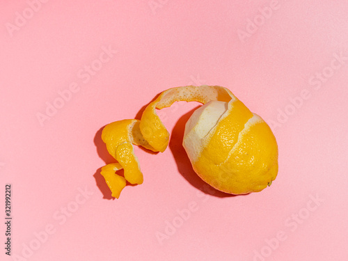 Cuadros en Lienzo Lemon with spiral peeled zest over pink minimalistic background