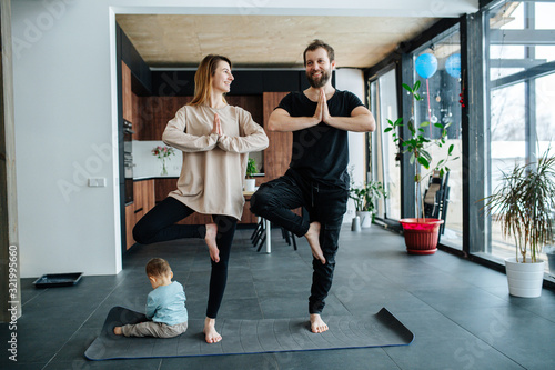 Parents standing in vrksasana position while their child plays next to them Wallpaper Mural