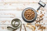 Fototapeta Kawa jest smaczna - Bowl with dry pet food, dog lead and brush on white wooden background