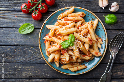 Fotografiet Penne pasta in tomato sauce and cheese decorated with basil on a wooden backgrou