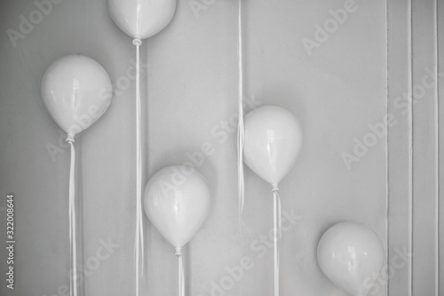 Photo Closeup shot of white balloons attached to the white wall