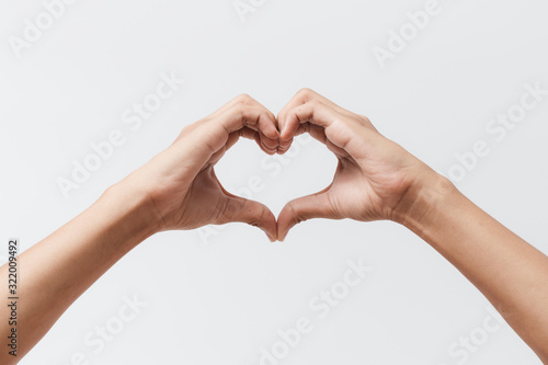 Obraz Man hands making a heart shape on a white isolated background - fototapety do salonu