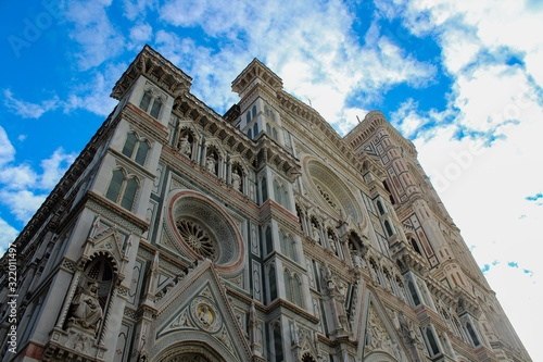 Low angle view of the Florence Cathedral under the sunlight and a cloudy sky in Florence in Italy
