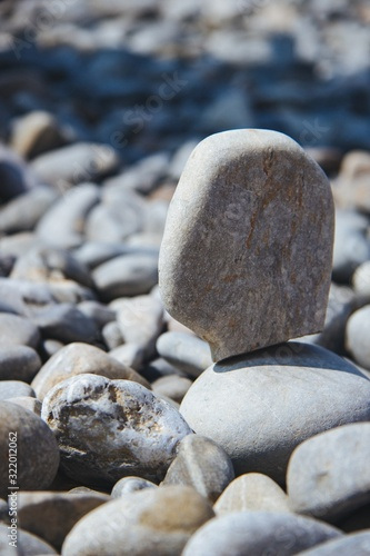 Vertical shot of a stone balanced on others during daytime