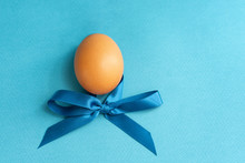 One Egg With A Blue Bow On A Blue Background, Easter Concept. Copy Space