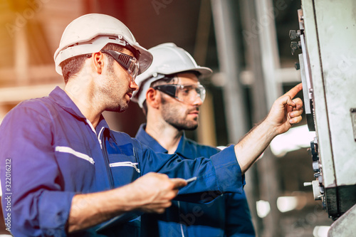 Photo industry engineer team worker teaching help friend operate control heavy machine