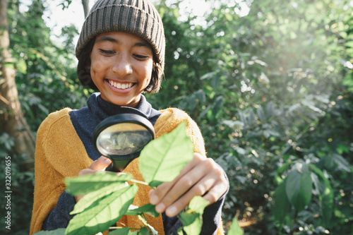 Foto Asian little girl exploring the nature with magnifying glass and happy smile In