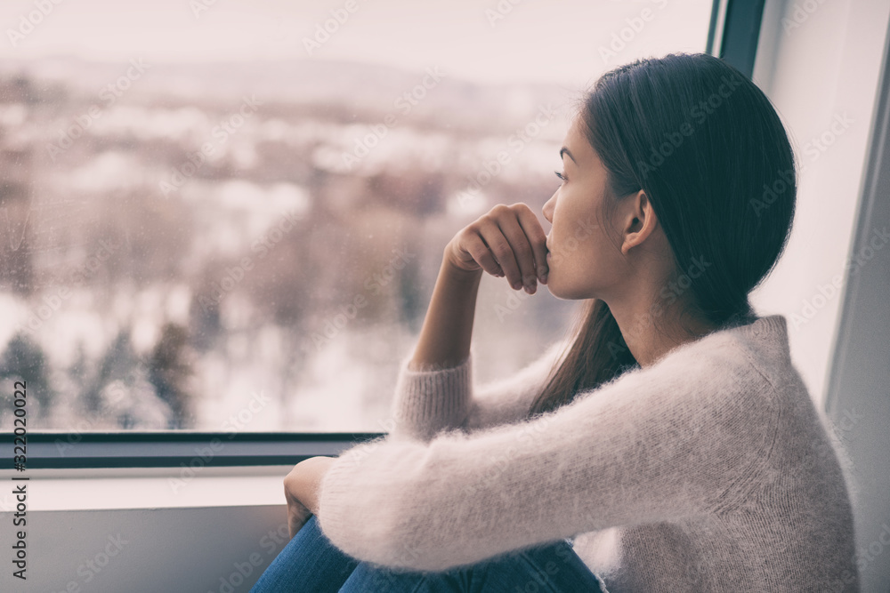 Fototapeta Winter depression - seasonal affective disorder mental health woman sad comtemplative looking out the window alone.