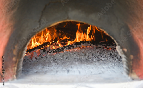 fireplace with log wood burning clay stove fire in home in the winter - fireplac Canvas Print