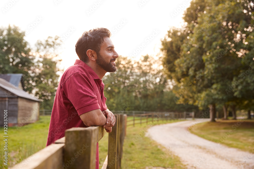 Fototapeta Smiling Man Taking A Break And Resting On Fence During Walk In Countryside