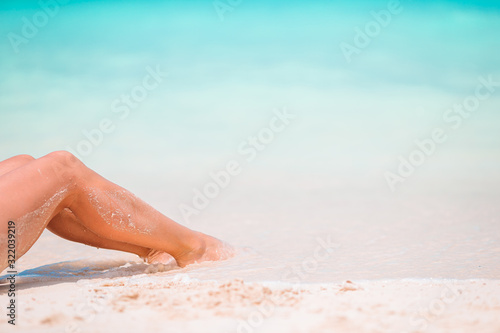 Valokuva Woman's feet on the white sand beach in shallow water