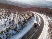Oblique View Of A Road With A Truck On It That Curves Around A Mountain Slope In A Early Winter Morning Where There Is Sunlight Falling On Freshly Fallen Snow