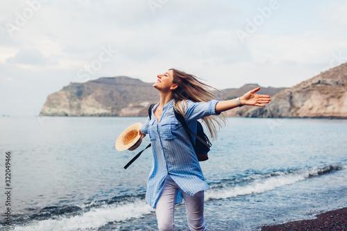 Fototapeta Traveler woman running along shore of Red beach on Santorini island, Greece. Traveling and vacation concept obraz