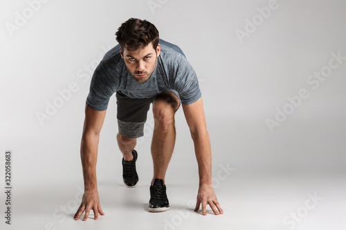 Fotomural Confident young sportsman standing ready to start running