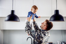 Young Soldier Just Arrived Home And He Is So Happy To See His Son. Man Is Lifting Toddler.