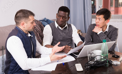 Three seriouse men are working with project and talking about documents together Fototapeta