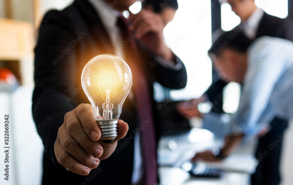 Fototapeta Innovation and idea of professional leader holding lighting bulb, business people planing and analysis work on table in office, brainstorming teamwork and thinking management concept