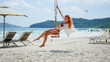 Long red haired woman sitting on the swing on the tropical Bai Sao beach on Phu Quoc island, Vietnam.