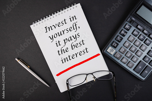 Notebook with the inscription Invest in yourself it pays the best intrrest on a black table Canvas Print