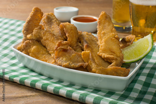 Fototapeta Fried Tilapia strips in platter with beer and sauces in wood background with half light obraz
