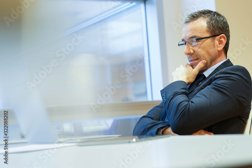Businessman at work being thoughtful in front of laptop