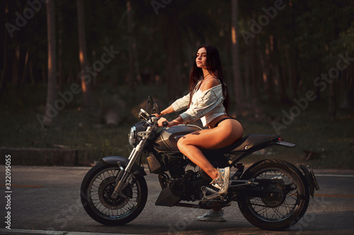 Fotografia Sexy fit woman with a black motorcycle in cafe racer style