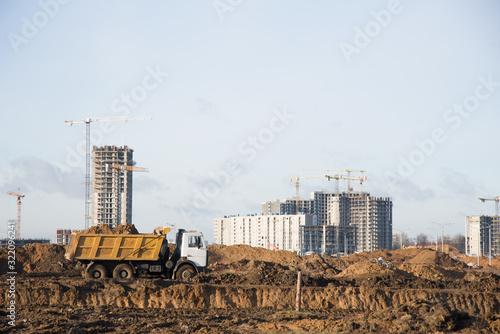 Obraz na płótnie Heavy dump trucks and hydraulic luffing jib tower cranes works at a construction site