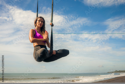 aero yoga beach workout - young attractive and athletic woman practicing aerial Canvas Print