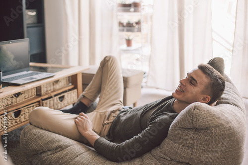 Photo Handsome teenage guy relaxing on modern soft couch at home in living room