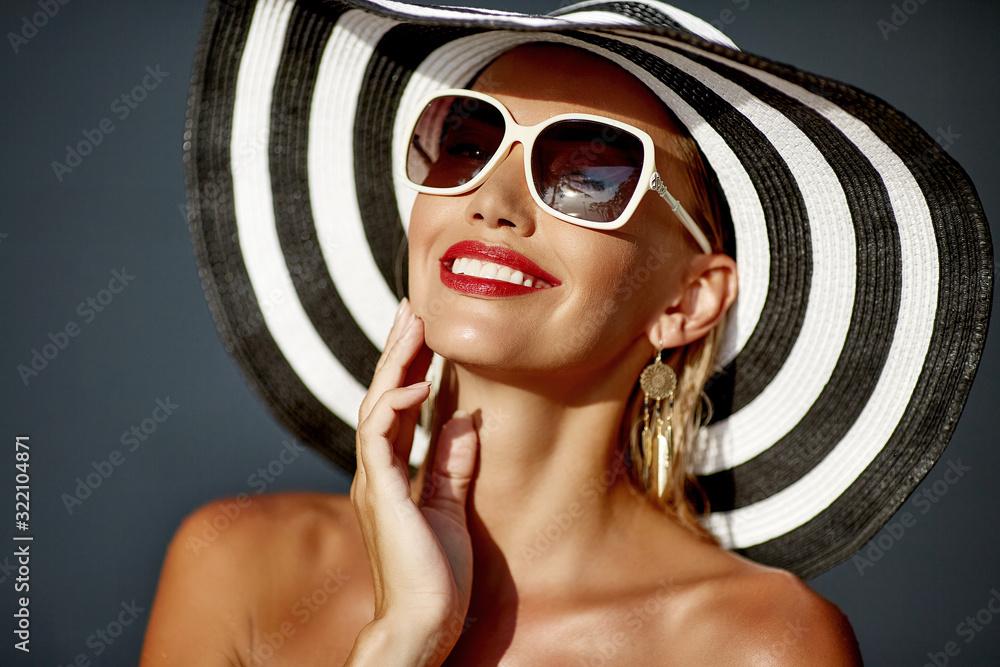 Fototapeta Beautiful smiling woman in hat and sunglasses - close up portrait