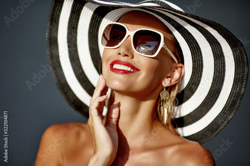 Obraz Beautiful smiling woman in hat and sunglasses - close up portrait - fototapety do salonu