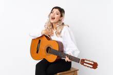 Teenager Girl With Guitar Over Isolated White Background With Surprise Facial Expression