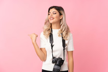 Teenager Girl Over Isolated Pink Background With A Professional Camera And Pointing To The Side
