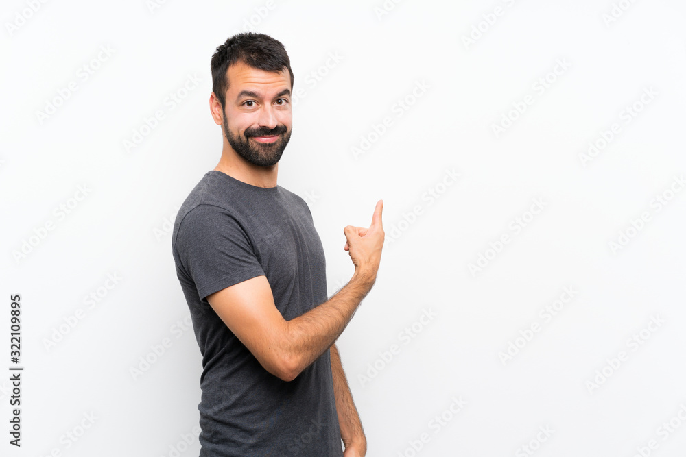 Fototapeta Young handsome man over isolated white background pointing back