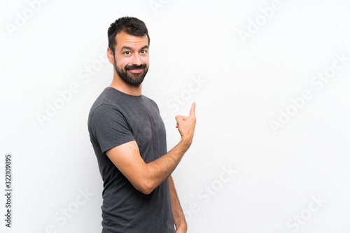 Tableau sur Toile Young handsome man over isolated white background pointing back