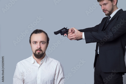 Fototapety, obrazy: business man in a suit aiming a gun at the head of another man in a white shirt. on a gray background. The concept of killing.